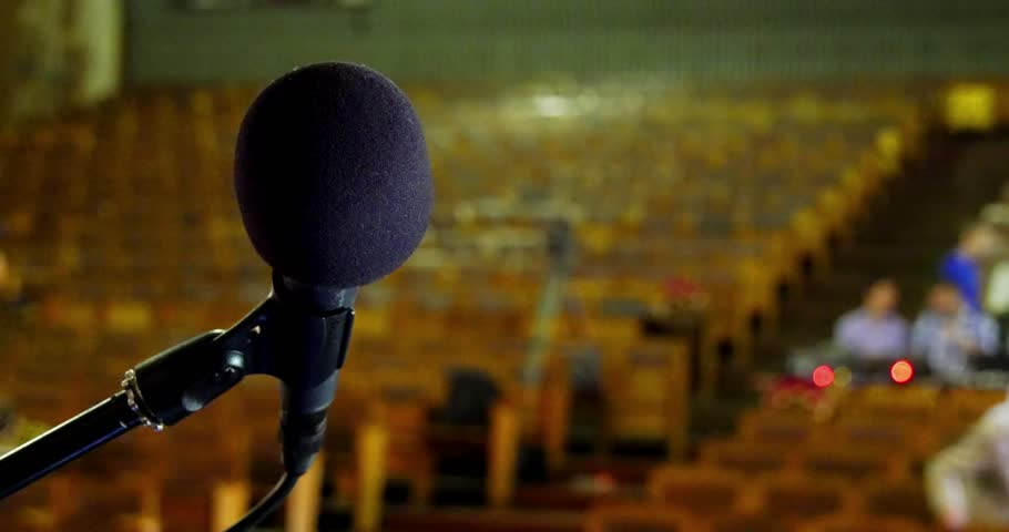 Microphone on a stand in front of an empty hall    Shutterstock HD Video #10196027