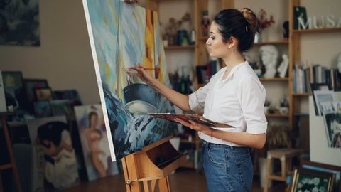 Cheerful young woman artist is painting beautiful picture marine landscape using oil paints then looking at masterpiece and smiling enjoying her work.