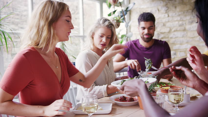 Young adult friends sharing tapas dishes for lunch at a restaurant table, selective focus | Shutterstock HD Video #1019647627