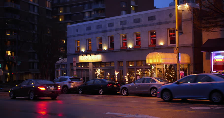 WASHINGTON, DC - Circa 2018 - An evening outside exterior (NX) side establishing shot of a typical city corner bar or restaurant on a late winter day. Day/Night matching available.
