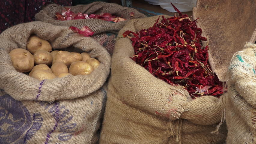 Close-up steady shot of displayed vegetables by vendors, large, well-rounded Irish potatoes, fresh, pink onions bulbs, deep red-hot Indian chili pepper,  sacks stacked closer, awaiting buyers, ope | Shutterstock HD Video #1019700637