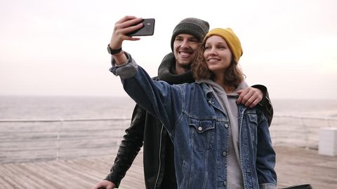 Happy young couple taking selfie by mobile phone near the seaside in cloudy day. Girl in yellow hat holding the smartphone, making funny faces. Beautiful couple selfie, love and bicycle concept