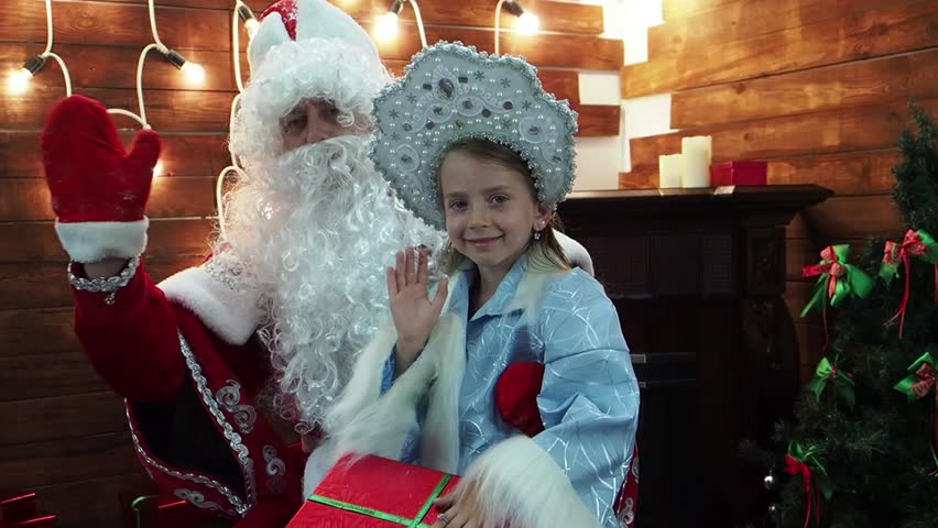Father Frost Santa Claus and Snegurochka wave a hand and smile. New Year's Christmas fairy tale characters in the house at a fireplace joyfully welcome the viewer.
