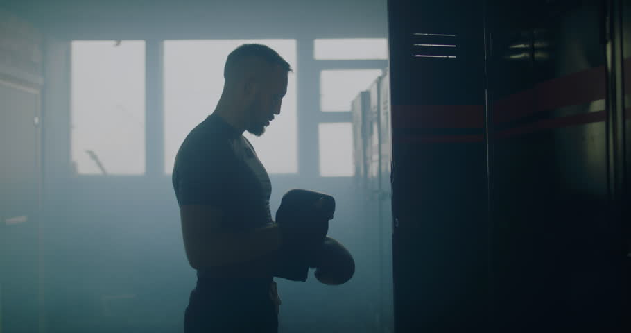 Caucasian male throws boxing gloves intro locker, dissatisfied with his training results. 4K UHD 60 FPS SLOW MOTION | Shutterstock HD Video #1019776567