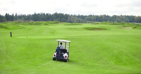 Golf player on cart gathering balls after game. Beautiful view of golf course.