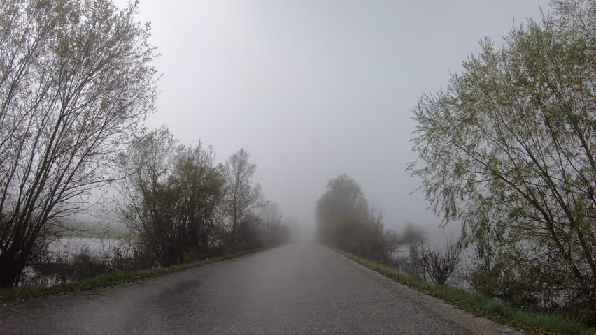 POV Driving on an asphalt road in fog across a flooded countryside