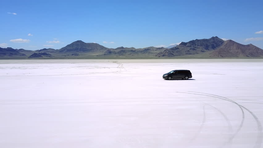 Drone follows modern minivan car moving along atmospheric landscape of flat salt lake desert on perfect USA road trip.