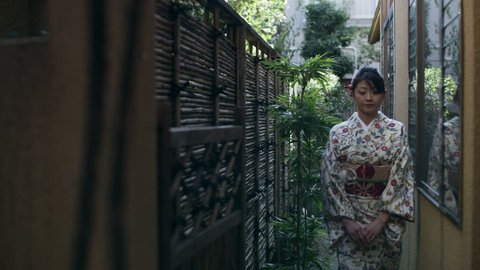 Woman in floral kimono walks through a pathway from a home garden near a traditional Japanese home with soft day lighting. Wide shot on 4k RED camera.