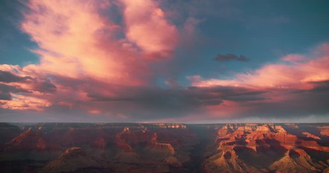 Gorgeous time-lapse of clouds racing over a Grand Canyon vista at sunset with beautiful lighting, clouds, red cliffs and blue skies in 4K DCI.
