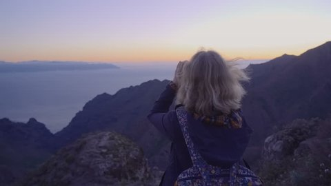 Mature woman in hiking adventures on a mountain top looking at the horizon through binoculars