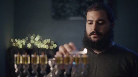 orthodox jewish person light a hanukkah menorah with olive oil candles.