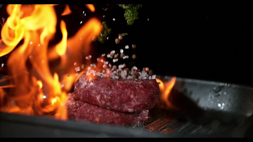 Super slowmotion footage of throwing fresh beef meat burger and herbs on ignited pan, 1000fps 4k