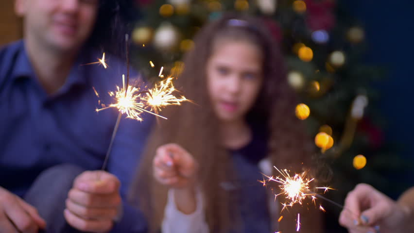 Blurry happy family with daughter enjoying great time togehter with bengal lights while celebrating Christmas eve at home over festive decorated room. Focus on sparklers. #1019967007