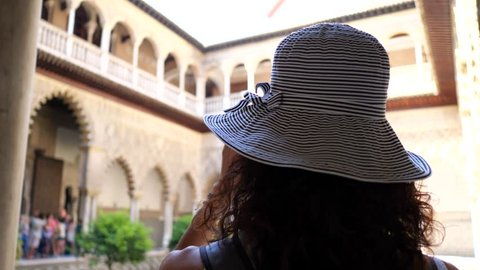 GRANADA, SPAIN - JUNE, 2018: Young woman taking picture inside Alhambra Palace, UNESCO site in Granada, Andalucia.