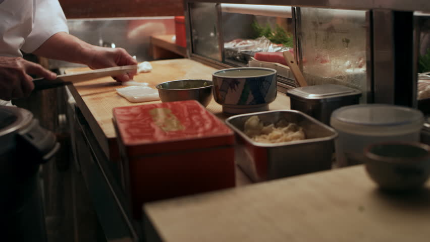 Sushi chef slicing pieces of Red Snapper and Tuna fish and rolling a ball of rice to make sushi for two customers in small sushi bar with soft interior lighting. Close up shot on 4k RED camera.