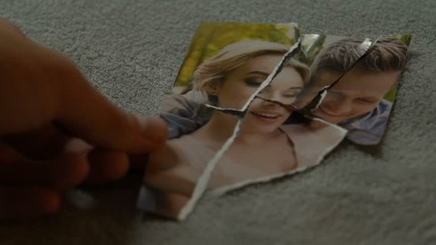 Male hands connecting tearing pieces of photo with his girlfriend, yearning