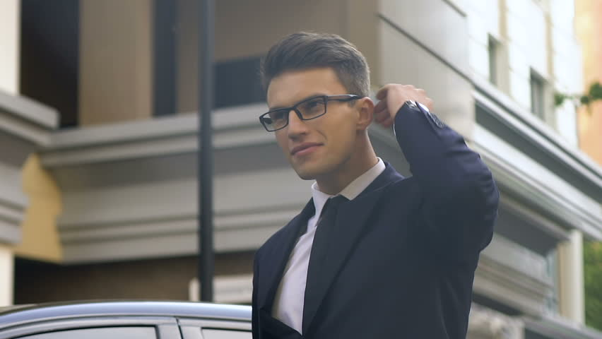 Confident business man in suit reaches destination place, checking time on clock