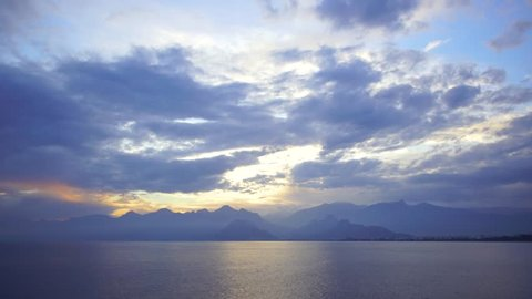 Beautiful sunset sunny sea water, mountains, cloudy fluffy sky and Antalya city landscape. Real time 4k video footage.