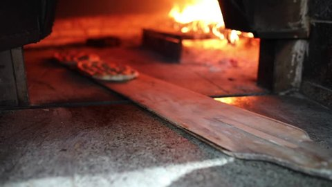 Traditional Turkish Pita or pide bread with sesame on wooden oar in brick oven or stone stove oven. Bakery or bakehouse concept image. Turkish cuisine ramadan iftar product.