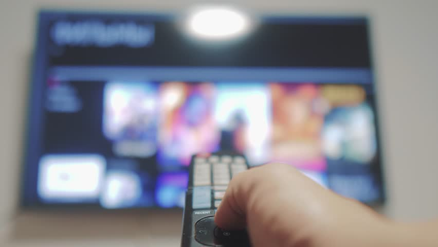 Smart tv with apps and hand. Male hand holding the remote control turn off smart tv . man hand controls TV holding remote. TV concept internet online lifestyle cinema | Shutterstock HD Video #1020086347