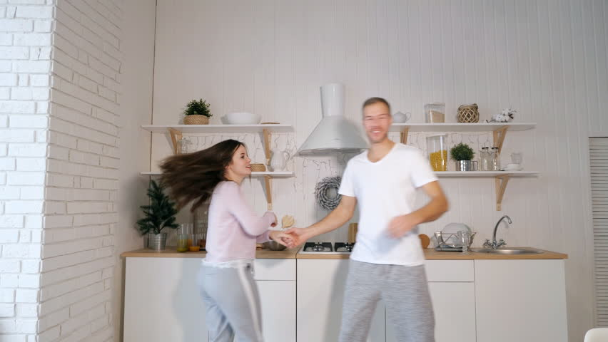 Handsome man and young woman smiling and dancing while standing on stylish kitchen at home | Shutterstock HD Video #1020093637