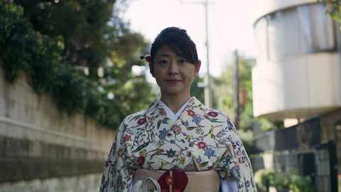 Portrait of woman in floral kimono standing in a quiet residential street in Japan, with soft day lighting. Medium shot on 4k RED camera.