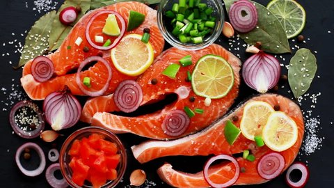 Cook preparing raw pieces of red fish salmon, sprinkles with seasonings, sesame, top view
