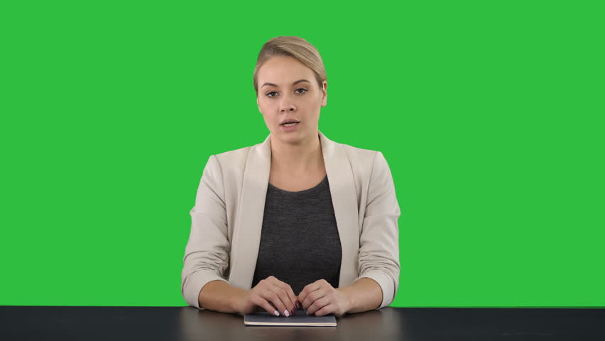 Young beautiful television announcer giving a speach on a Green Screen, Chroma Key.