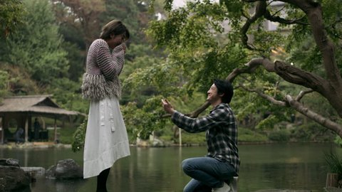 Cheerful Japanese man proposes to his girlfriend and they hug happily in a beautiful garden in the rain with soft natural lighting. Wide shot on 4k RED camera.