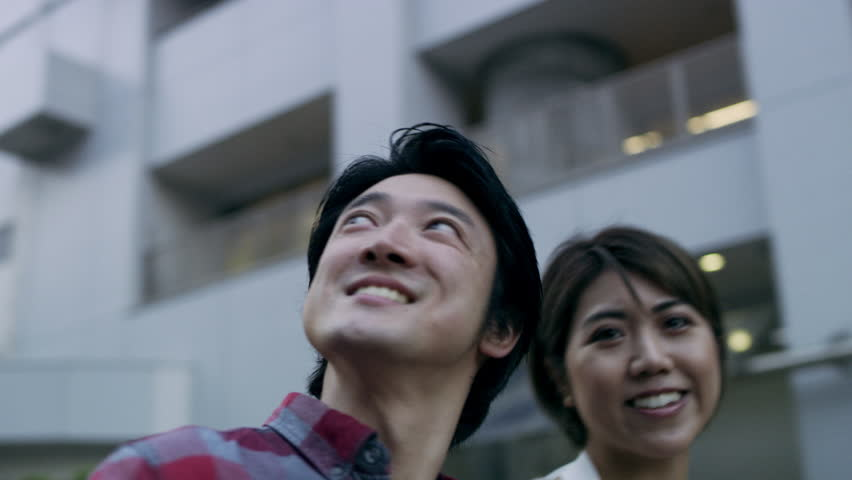 Happy Japanese couple looking up at buildings together in a quiet metropolitan street in Japan with soft natural lighting. Medium shot on 4k RED pan around camera.