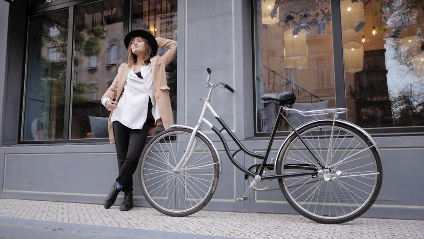 Young woman hipster in hat posing on the street with bicycle | Shutterstock HD Video #1020302827