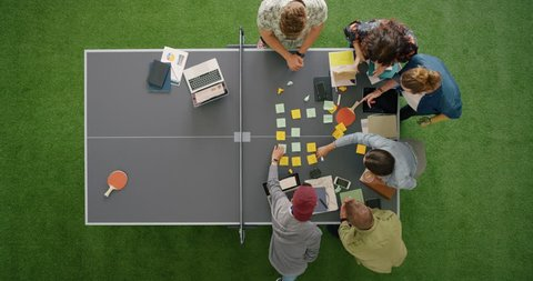 young multi ethnic team of web developers brainstorming ideas for startup business website planning design layout on ping pong table in modern workplace overhead