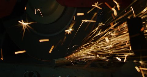 Industrial worker grinding metal with a lot of sharp sparks (extra macro tool close up)