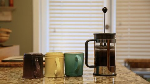 A french press on a kitchen counter top being pressed followed by coffee being poured into a cup.