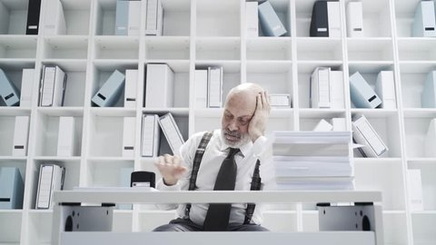 Lazy office worker doing a repetitive dull job, he is stamping a pile of paperwork