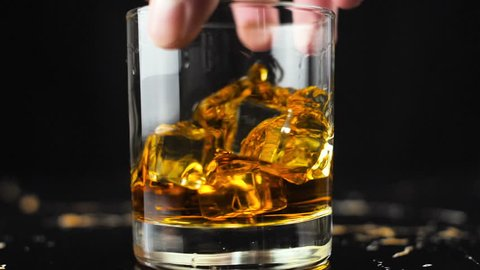 Man hand hold glass with whiskey on gold marble surface in slow motion.