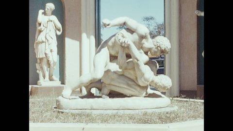 1950s: Grecian statues in building courtyard. Statue of men wrestling. Pedestrians and traffic traverse narrow streets in city.