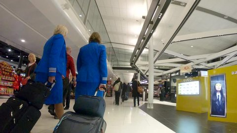 MONTREAL, CANADA - November 2018 :Flight attendants in uniform walking in an airport terminal to their flight.