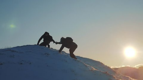 teamwork lifestyle business travel concept. two hikers gives hand winter snow tourists climbers climb to the top of the mountain. overcoming hardships the path to victory, teamwork, important points