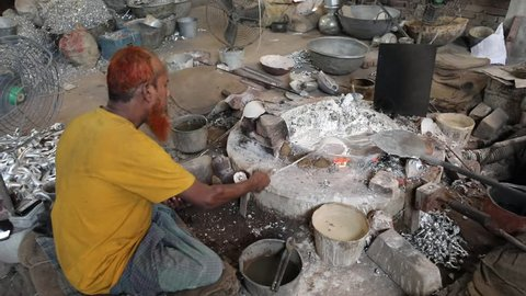 DHAKA, BANGLADESH - DECEMBER 01, 2018: Aluminium factory sweatshop with children and adultsworking in dangerous and unsafe circumstances making aluminium teapots