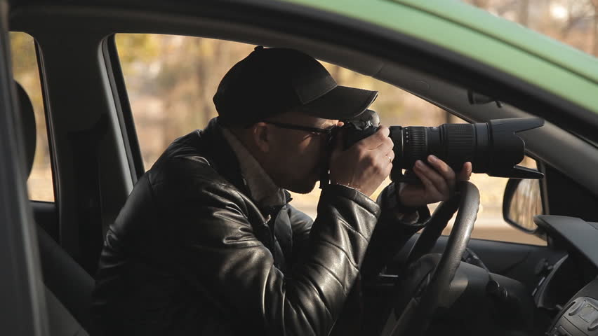 A private detective or a spy conducts surveillance of the object of surveillance. A man secretly taking pictures from the car window | Shutterstock HD Video #1020566707