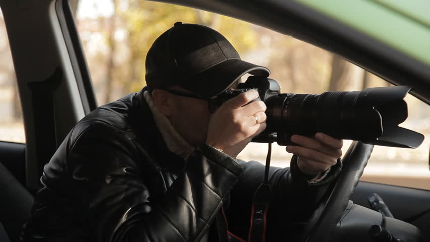 A private detective or a spy conducts surveillance of the object of surveillance. A man secretly taking pictures from the car window | Shutterstock HD Video #1020566737