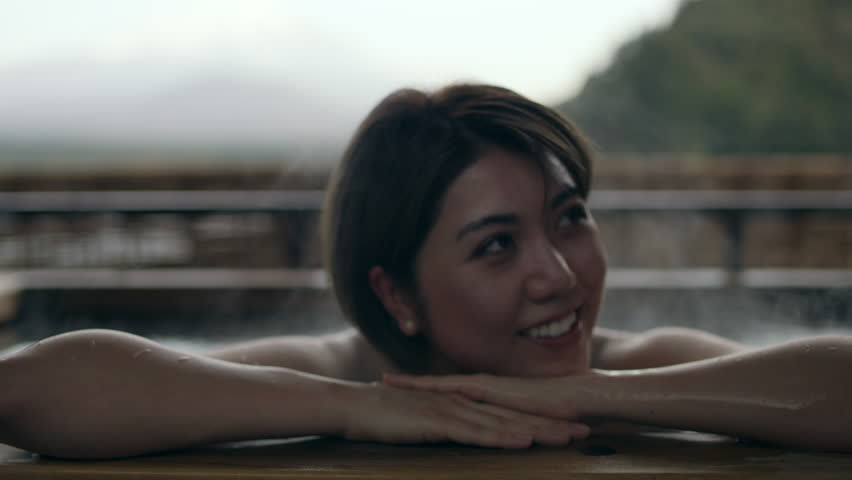 Close up shot on 4k RED camera. A pensive Japanese woman in a sitting in a hot water bath at a traditional spa outside with soft natural lighting.