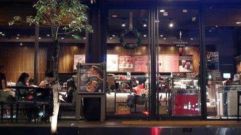 Taipei, Taiwan - November 01, 2018 : Motion of people enjoying coffee inside Starbucks coffee at night with 4k resolution.