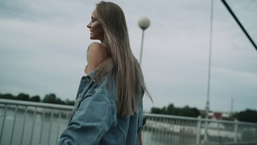 the girl goes and throws her arms happily apart and throws her hair away. frame from the back, slow motion. #1020601507