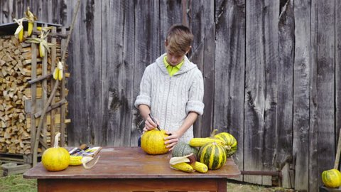 Boy draw lines and start cutting pumpkin HD. Wide shot of young man in woolen sweater drawing lines on top of pumpkin and stabs a knife to cut out top part for Halloween. Wooden background.