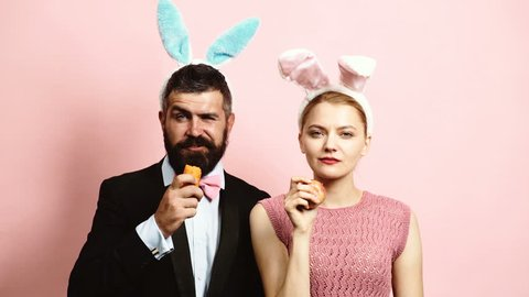 Bearded man and girl with rabbit ears eat carrots and an apple on pink background. Hares eat fruits. Concept of healthy eating