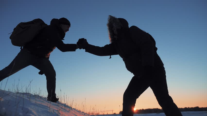 Teamwork business travel silhouette concept. two hikers winter snow tourists climbers climb to lifestyle the top of mountain. overcoming hardships the path to victory, teamwork, important points in | Shutterstock HD Video #1020639787