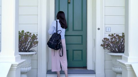 asian woman leaving home to work and locking door of apartment. white house with green front door; traditional house design. security safety lock concept.
