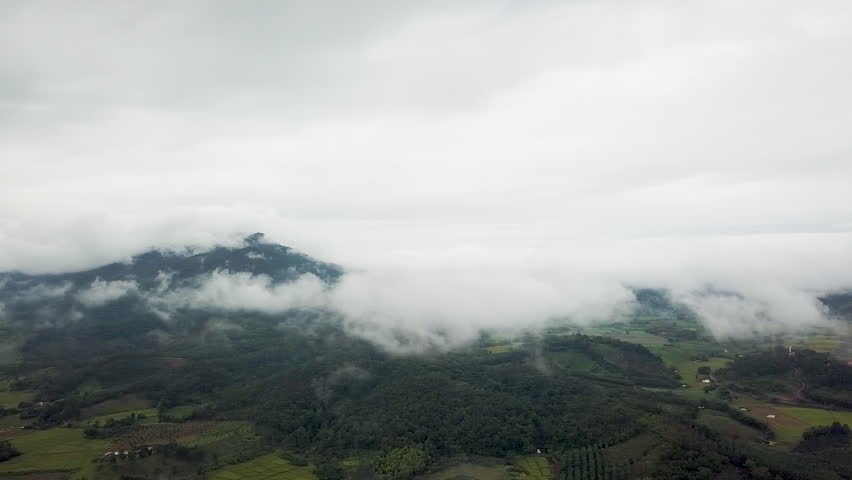 A panoramic rotational view high above the white fluffy scattered clouds looking down at farmland and rice crops in Chiang Rai Thailand | Shutterstock HD Video #1020658687